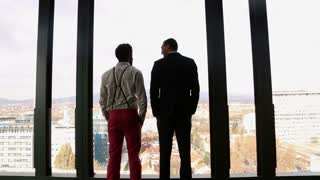 Back view of two businessman looking on city through window and talking