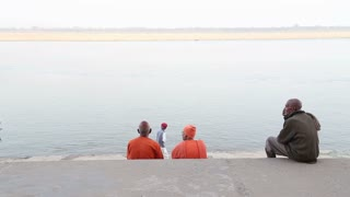 Back view of two men sitting on the ghats of the Ganges river in Varanasi.