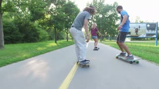 Back view of woman and two guys skateboarding