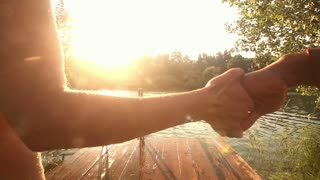 Back view of young couple holding hands and jumping into water from river dock at sunset, graded, in slow motion