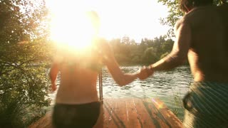 Back view of young couple holding hands and jumping into water from river dock at sunset, graded