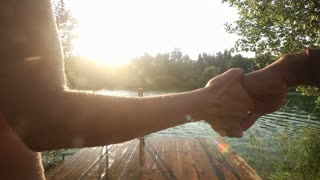 Back view of young couple holding hands and jumping into water from river dock at sunset, in slow motion