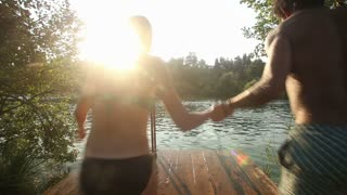 Back view of young couple holding hands and jumping into water from river dock at sunset