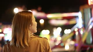 Back view of young woman looking at carousel in amusement park