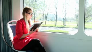 Beautiful blond woman reading book while riding tram