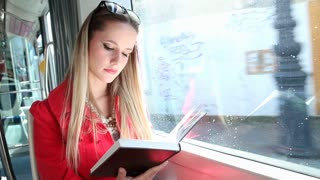 Beautiful blond woman riding tram, reading book on sunny day