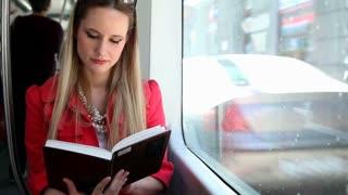 Beautiful blond woman riding tram, reading book