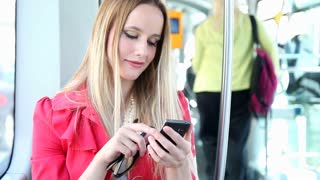 Beautiful blond woman riding tram, typing on mobile, phone, cell, biting lips