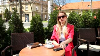 Beautiful blond woman sitting in coffee shop, answering the phone and waving