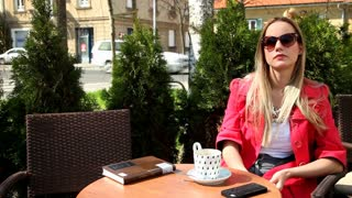 Beautiful blond woman sitting in coffee shop, answering the phone