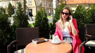 Beautiful blond woman sitting in coffee shop, talking on the phone