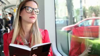 Beautiful blond woman smiling while reading book and driving in tram