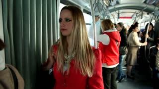 Beautiful blond woman standing in tram