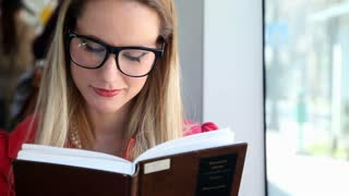 Beautiful blond young woman reading book sitting in tram, looking at camera