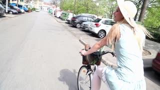 Beautiful blonde girl riding bike on the street