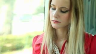 Beautiful blonde woman riding tram, reading book