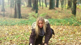 Beautiful blonde woman smiling and throwing leaves in the park, graded