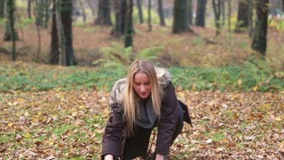 Beautiful blonde woman smiling and throwing leaves in the park