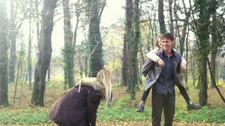 Beautiful blonde woman throwing leaves at her cute daughter and husband in the park, graded