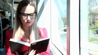 Beautiful blonde young woman reads book while riding tram