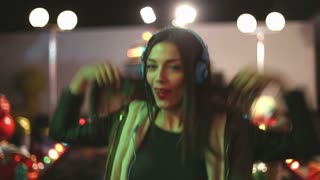 Beautiful brunette woman dancing to the rhythm of music with headphones in amusement park