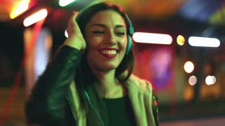Beautiful brunette woman dancing to the rhythm of music with headphones, sending kiss to camera, slow motion, graded