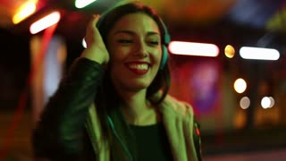 Beautiful brunette woman dancing to the rhythm of music with headphones, sending kiss to camera, slow motion