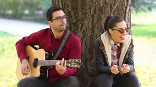 Beautiful brunette woman laughing and handsome man playing guitar while sitting on a tree in park, slow motion