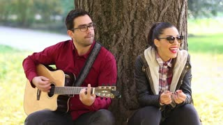 Beautiful brunette woman laughing and handsome man playing guitar while sitting on a tree in park