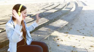 Beautiful brunette woman listening to music on headphones and dancing to the rhythm at park, graded