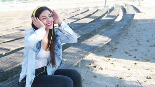 Beautiful brunette woman listening to music on headphones and dancing to the rhythm at park