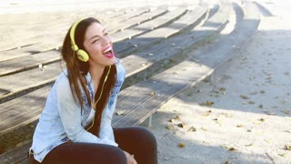 Beautiful brunette woman listening to music on headphones and singing at park, graded