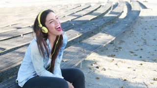 Beautiful brunette woman listening to music on headphones and singing at park