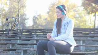 Beautiful brunette woman listening to music with headphones at the park