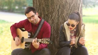 Beautiful brunette woman singing and handsome man playing guitar while sitting on a tree in park, graded
