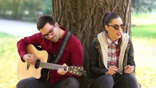 Beautiful brunette woman singing and handsome man playing guitar while sitting on a tree in park