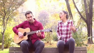 Beautiful brunette woman singing and man playing guitar in park, sitting next to her on bench in park, in slow motion, graded