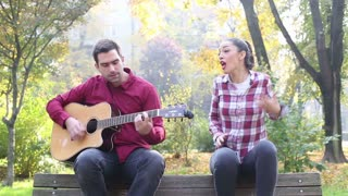Beautiful brunette woman singing and man playing guitar in park, sitting next to her on bench in park, in slow motion