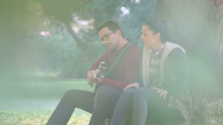 Beautiful brunette woman singing and man playing guitar while sitting on a tree in park