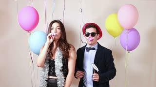 Beautiful couple blowing party horns in photo booth