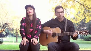 Beautiful couple having fun sitting on park bench and playing guitar on sunny autumn day, graded