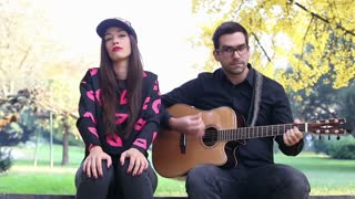 Beautiful couple having fun sitting on park bench and playing guitar on sunny autumn day