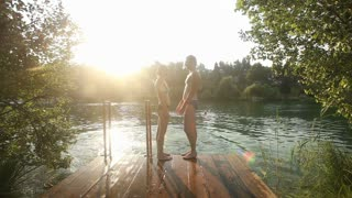 Beautiful couple in love standing on the dock holding hands by the Mreznica river at sunset, talking, smiling and kissing