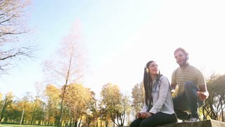Beautiful couple listening to music on headphones and moving in the rhythm at the park, graded