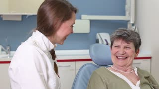 Beautiful female dentist laughing and talking with elderly female patient