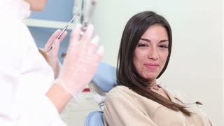 Beautiful female patient faking fear of injection at dentist