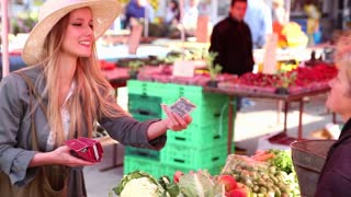 Beautiful girl at the market paying for vegetables