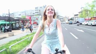 Beautiful girl riding bike on the street, holding hat