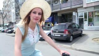 Beautiful girl riding bike on the street, waving