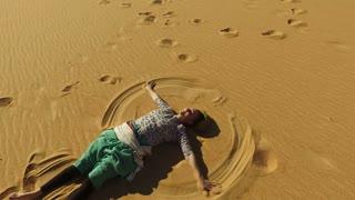 Beautiful happy woman making sand angel in desert, Egypt